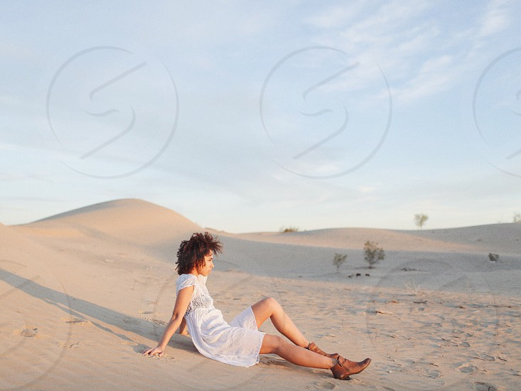woman in white blouse sitting on sand under cloudy blue sky photo