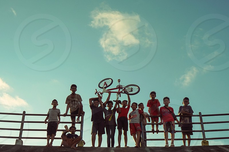group of boys raising up bicycle near metal railings under blue skies in low angle photo photo