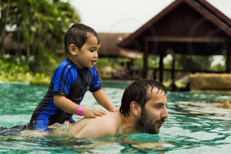 father and son have fun holidays at the swimming pool photo