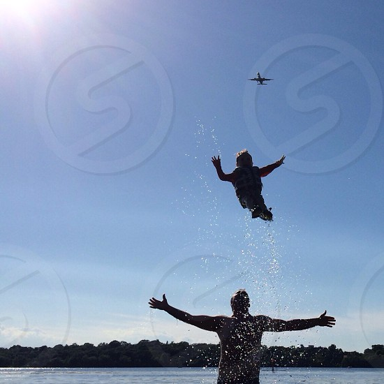 man in water about to catch child up in the air during daytime photo
