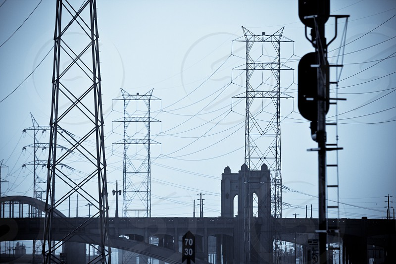 grey sky over power line towers and grey concrete bridge and train signals photo