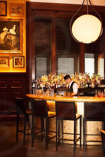 man wearing black suit vest in a bar near black metal bar stool photo