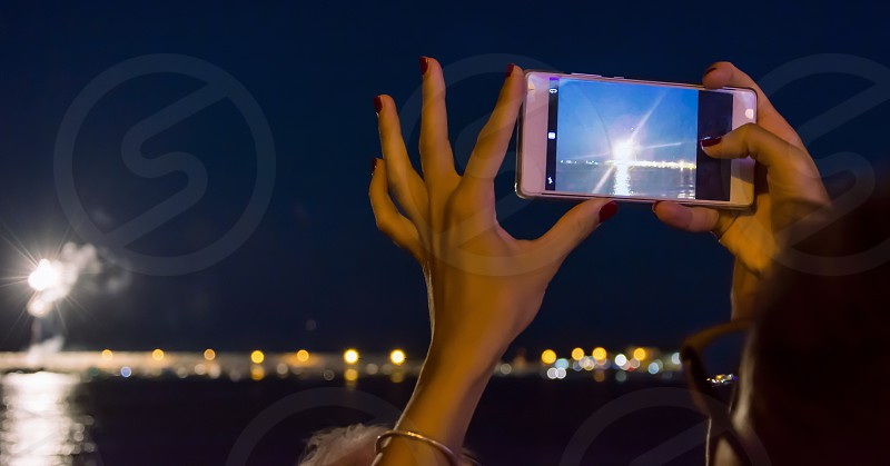 woman holding a mobile smart phone to take photo of firework photo