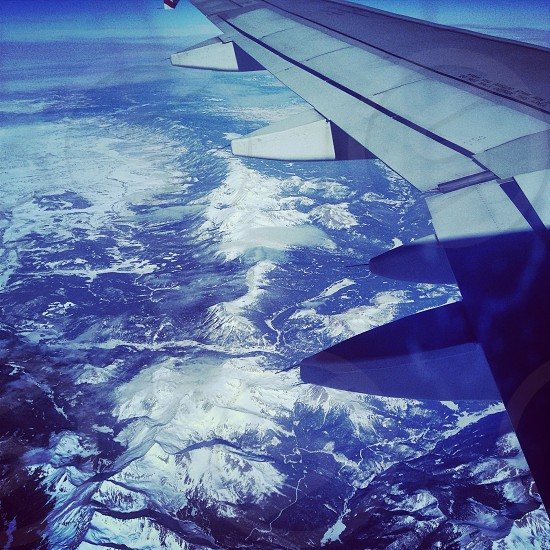 view of snow covered mountain ranges from an airplane photo