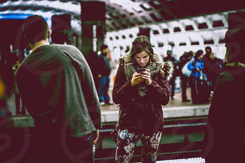 woman fiddling on phone at the subway station photo