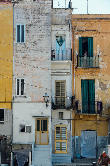 The texture and feel of the buildings create a strong understanding of the life of the people who live there. I was compelled to capture the contrast between the great history of this place and the harsher reality of living there. I wanted to capture the architectural style of the buildings that give Bari it a historical appeal by capturing the texture and charm of buildings with the dramatic tension of the people who call it their home. photo