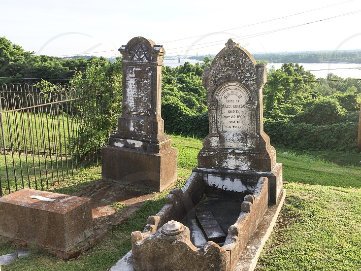 Gravestones overlooking the Mississippi River at the Natchez City Cemetery in Natchez MS.  photo