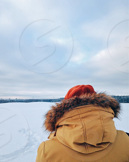 back of a person wearing a fur lined hooded yellow jacket and red beanie cap in white snow under a cloudy sky photo
