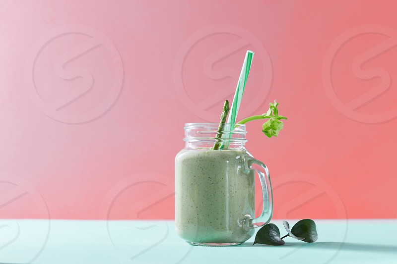 Vegetarian healthy mix from vegetables with green leaves and plastic straw in a glass jar on duotone background in a color of the year 2019 Living Coral Pantone. photo