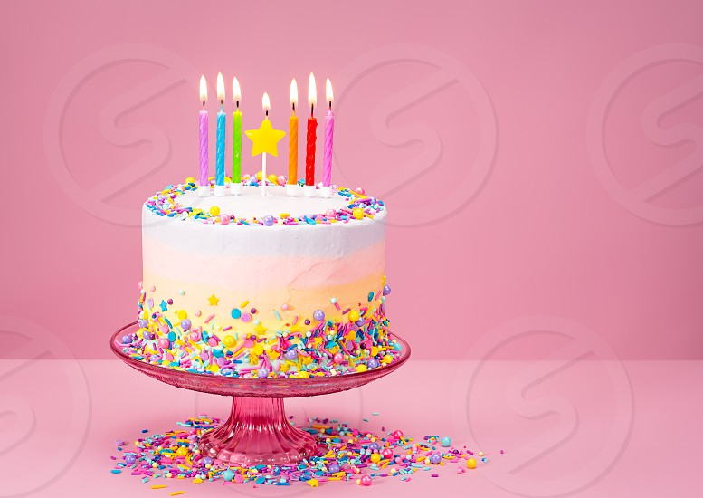 Colorful Birthday cake with sprinkles over a pink background. photo