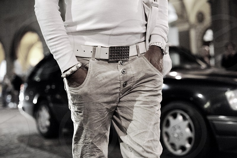 man wearing white sweater and denim jeans with white leather belt walking by the street with both hands in pocket in gray scale photography photo