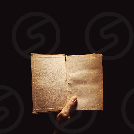 Conceptual composition about reading books a male hand holding a book in the dark.  photo