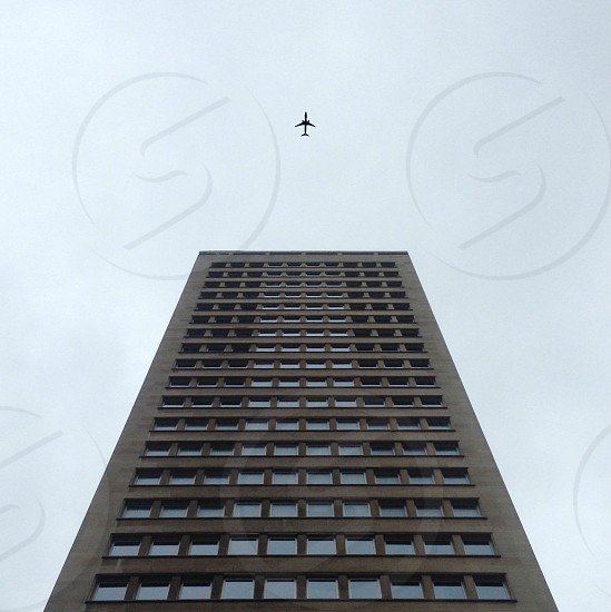 tall brown building below an airplane photo