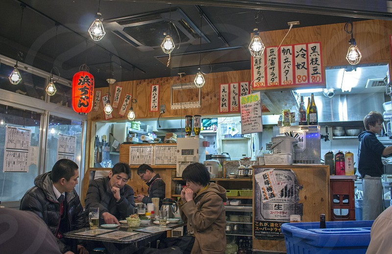 scene of a Japanese restaurant izakaya. people casually gathered there for social meeting eat and drink with friends after work. photo