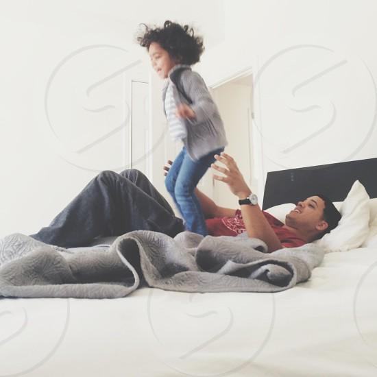 girl wearing grey jacket beside man lying on bed photo