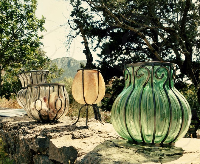 four brown and green glass vases on gray concrete frame photo