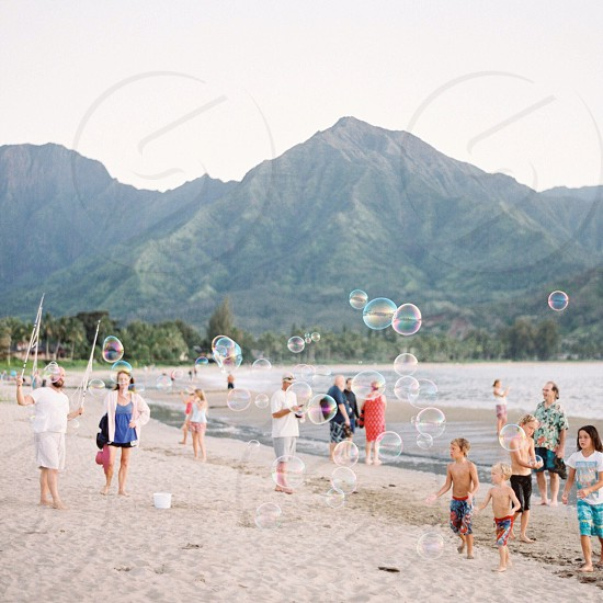 crowd blowing bubbles in white sand beach during daytime photo