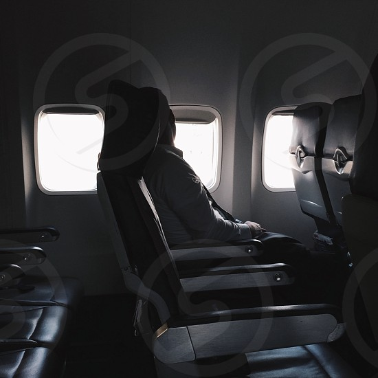 man lying on airplane seat photo