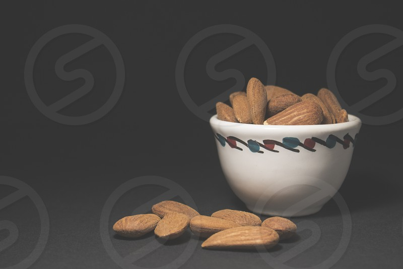brown raw almonds in a white ceramic bowl photo