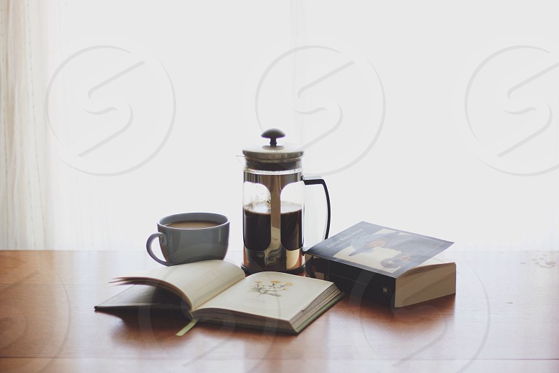 books on table beside coffee in ceramic mug during daytime photo