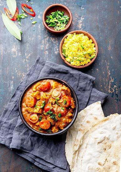 INDIAN FOOD. ROGAN JOSH curry sauce. Pork rogan josh with rice and naan bread. photo