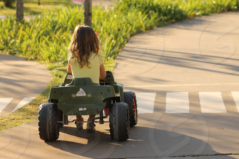 girl riding green toy car photo