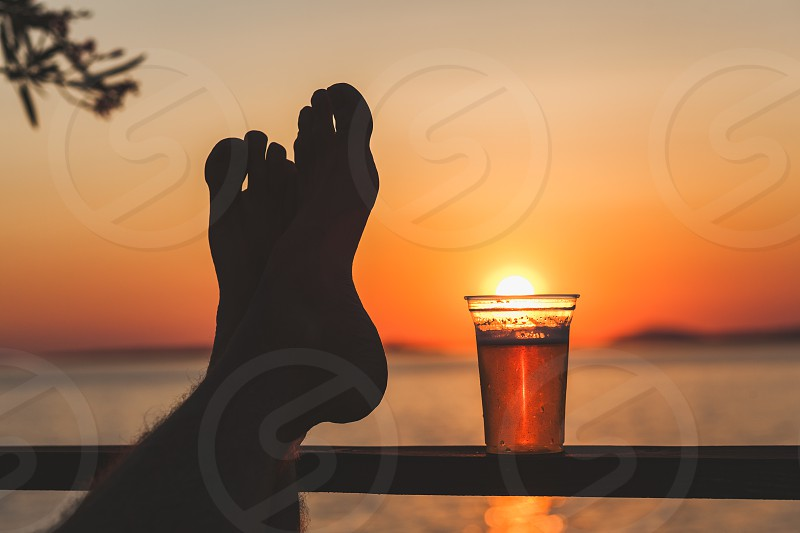 Man's feet and a beer cup with setting sun in the background photo