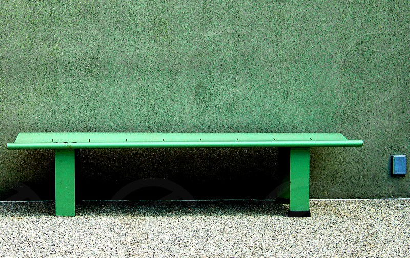simple green bench is pushed against a green stucco textured wall photo