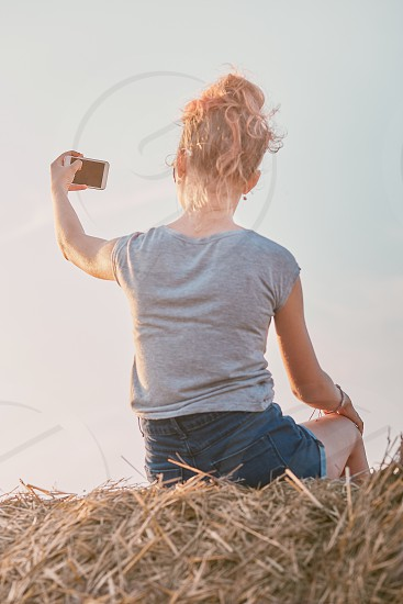 Teenage girl taking a selfie of herself sitting on a hay bale enjoying summer vacation in the countryside. Candid people real moments authentic situations photo