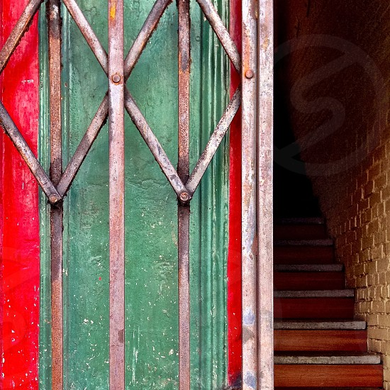 Red and green wall with security gate and stairway.  photo