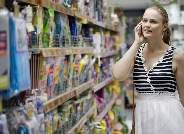 Woman with a long blond ponytail chatting on her mobile while out shopping standing in an aisle in the supermarket photo