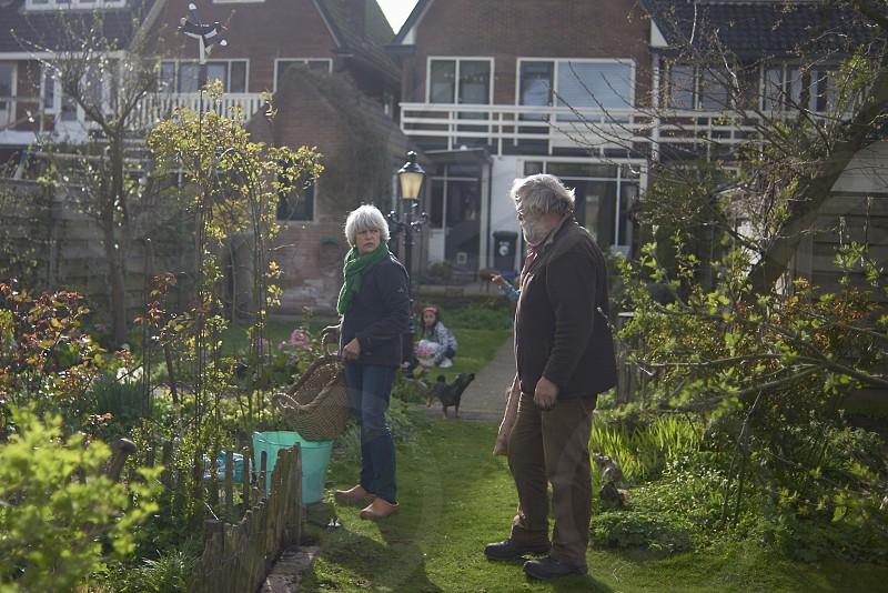 HEalthy elderly couple sitting on their knees hard at work gardening in their back yard photo