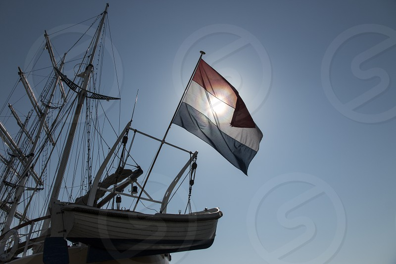 Dutch flag on a three  master in the harbour of Urk the Netherlands. The Dutch have been a sea faring nation more many centuries. photo