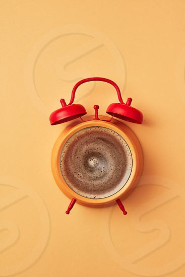 Vintage yellow alarm clock with red bells and cup of coffee on an yellow pastel background place for text. Concept of morning coffee. Top view. photo