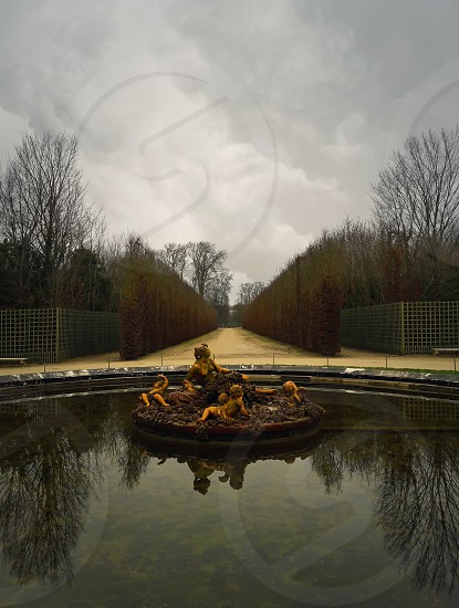 Fountain in the gardens of Versailles Palace in winter season with bare trees reflected in water. photo