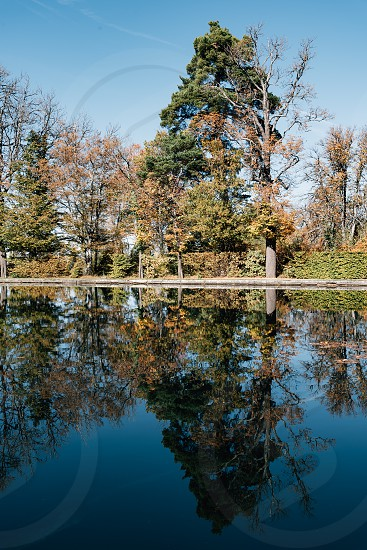 Pond in the Garden of Royal Palace of The Granja. Reflections on water a blue sky day of autumn photo