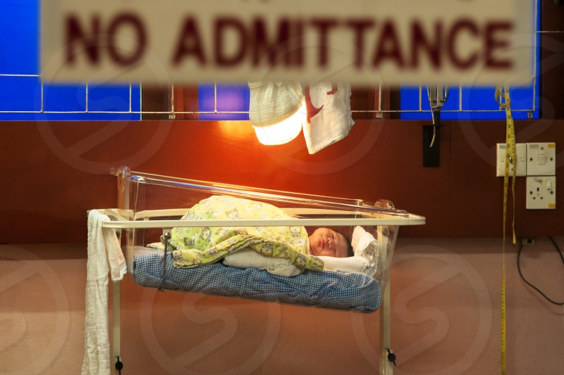 Newborn baby asleep in crib warmer photo