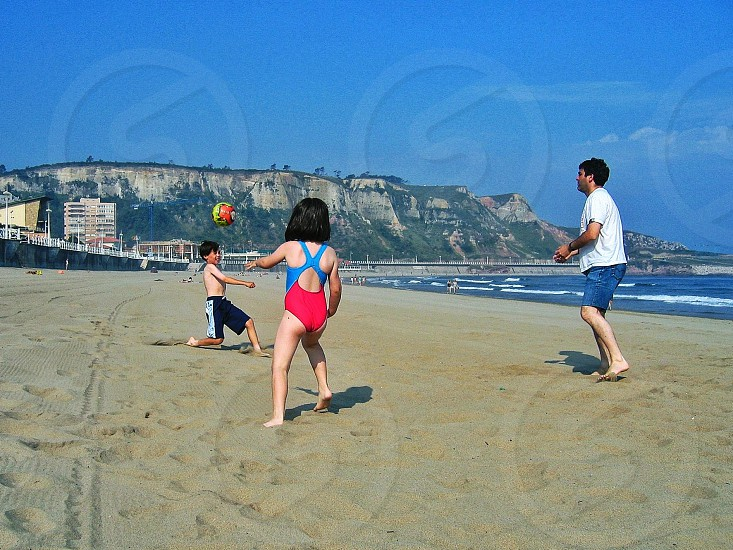 girl and boy playing volleyball near ocean photo