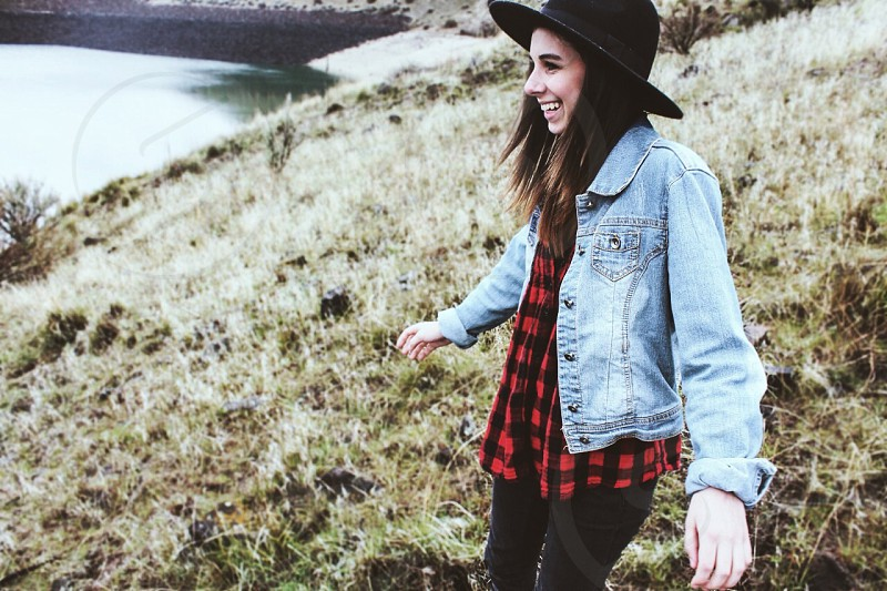 woman in red and black checked top and blue denim jacket and black leggings standing on grass field photo