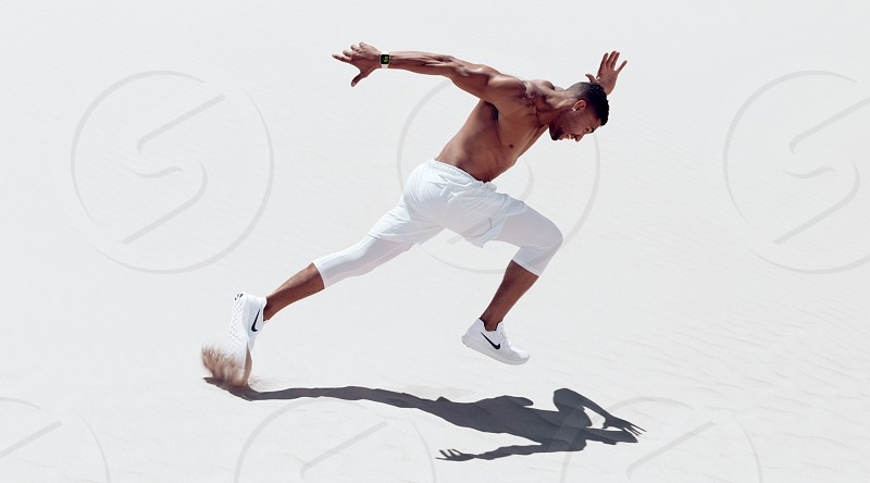 Athletic male fitness model working out and doing acrobatic flips on sand dune photo