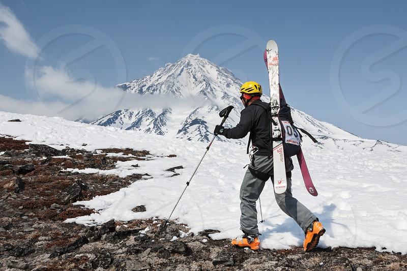AVACHA VOLCANO KAMCHATKA RUSSIA - APR 21 2012: Open Cup of Russia on ski-mountaineering on Kamchatka. Ski mountaineer climbing on mountain with skis strapped to backpack on background Koryak Volcano. photo