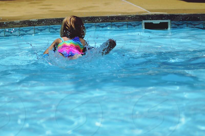 Summer fun child swimming swimming pool pool water splashing fun little girl swimsuit vacation resort splash no face unrecognizable people person  photo