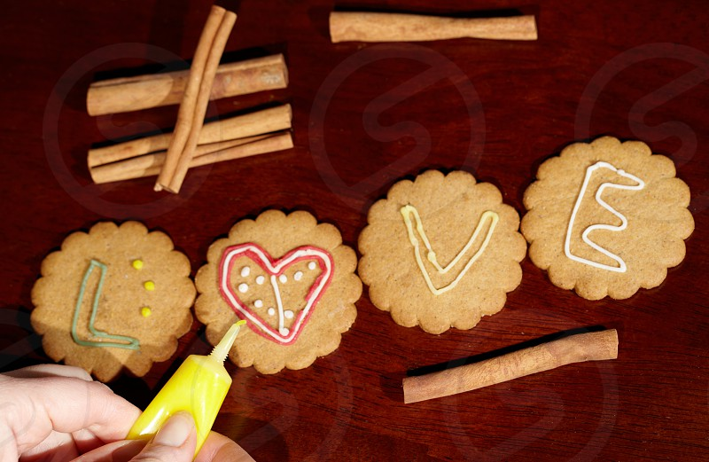 Drawing on ginger cookies. The word love. photo