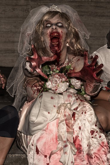 woman in a blood stained wedding gown in zombie costume photo