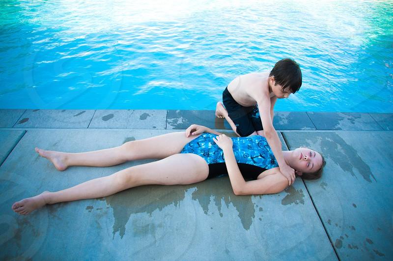 boy saving a girl near pool photo