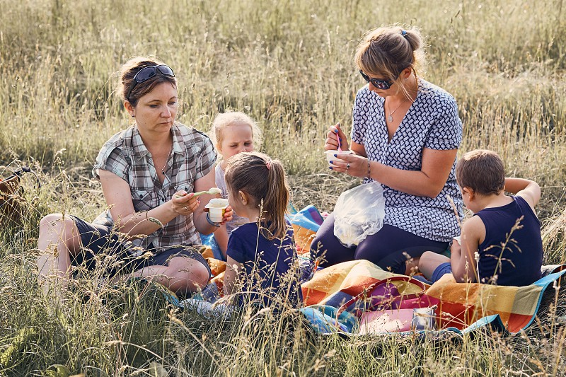 Families and friends spending time together on a meadow close to nature. Mothers feeding kids sitting on a blanket on grass. Candid people real moments authentic situations photo
