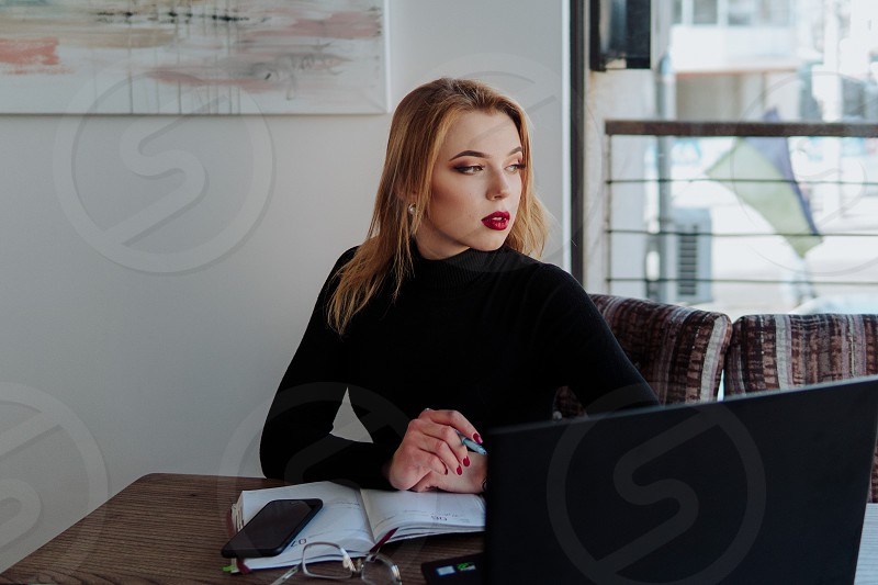 Young beautiful business lady is tired of work looking through the window photo