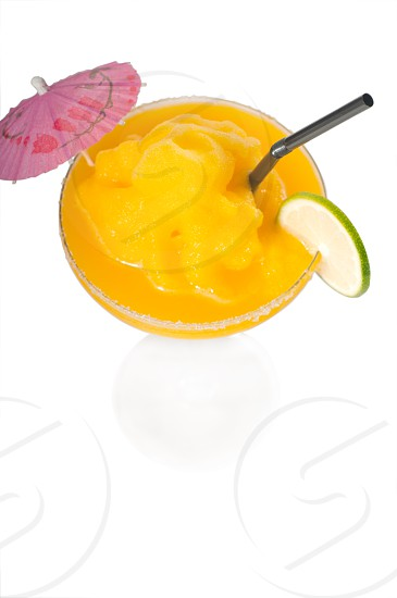 frozen mango margarita daiquiri with lime black straw and pink umbrella isolated on white background photo