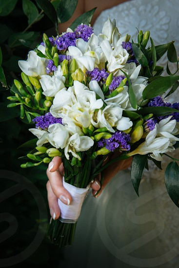 Simple bridal bouquet. White and purple flowers white ribbon. photo