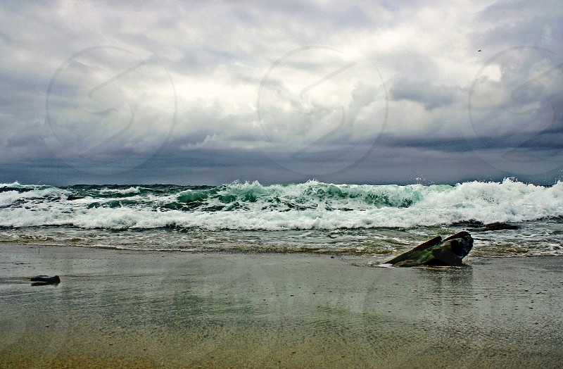 Low angle perspective of ocean waves on a sandy beach photo